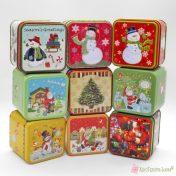 Μικρά τετράγωνα μεταλλικά κουτιά με χριστουγεννιάτικες παραστάσεις